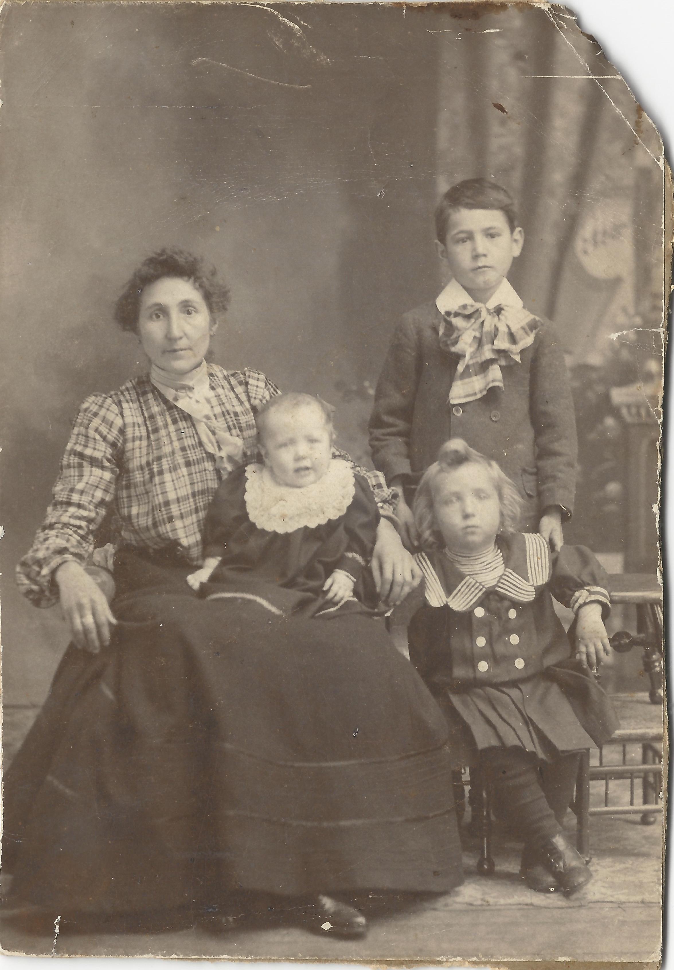 Cécile Gagnon Lizette avec trois de ses enfants. Debout John, l'aîné né en 1894, qui pourrait avoir 6 ans, ce qui daterait la photo de 1900 environ.  L'enfant assis à droite serait alors Wilfrid (1897-1900) et le bébé Pauline-Blanche (1899-1901).