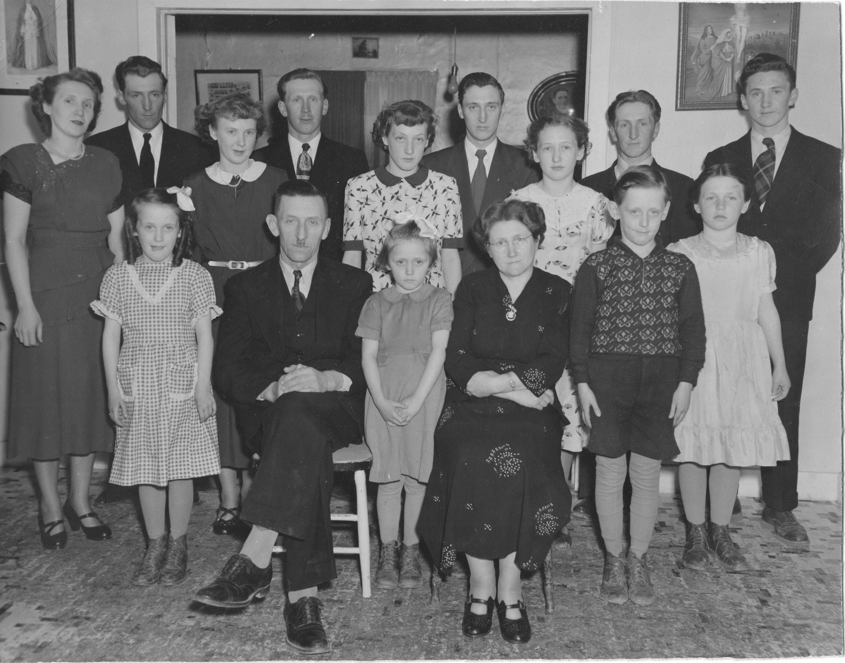 La famille d'Héraclius Doré et Blanche Lizette. En partant en haut à gauche, Éloi, Hubert, Paul-Émile, Laurent, Louis-Joseph; 2e rangée, Cécile, Françoise, Angèle, Lucie, Thérèse; devant, Claudette, Héraclius, Andrée, Blanche, Claude. Marthe est absente.